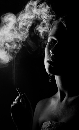 silhouette of a beautiful girl with a cigarette  photo