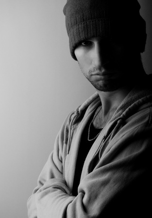 contemplation: sad young man in a hat in the dark Stock Photo