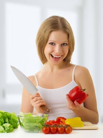 cutting boards: happy  woman preparing vegetarian food