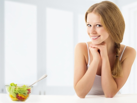 beauty young woman eating vegetable salad photo
