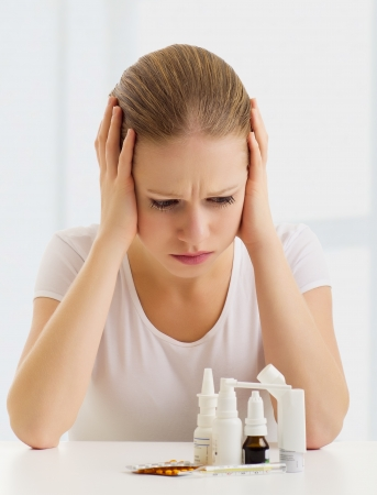 woman with a headache and with medicines photo