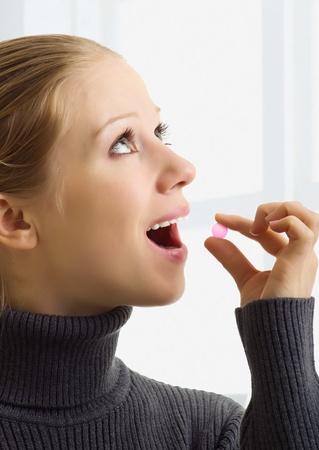 femme bouche ouverte: une belle jeune femme de prendre un comprimé