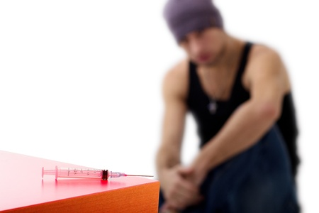 illegal substance: syringe and drug addict, sitting  Stock Photo