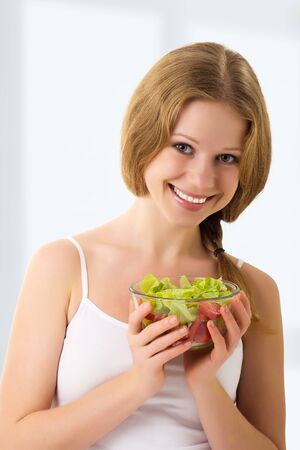 beautiful young woman with vegetarian salad photo
