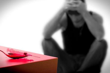 drogadicto: jeringa y adicto a las drogas, sentado