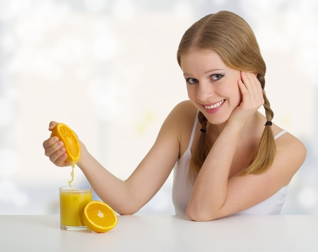 beauty girl squeezes the juice from the orange photo