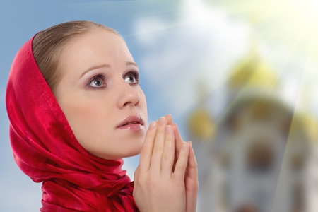 beautiful young woman in a scarf prays to God photo