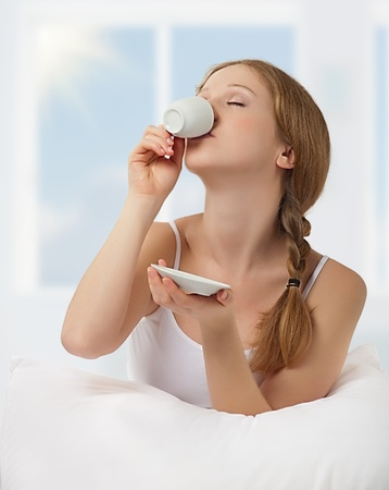 beautiful woman drinking  coffee in bed photo