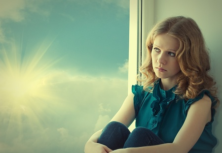 sad, beautiful young woman  at the window  photo
