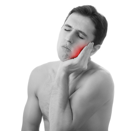 toothache: young man holding his aching tooth in pain,