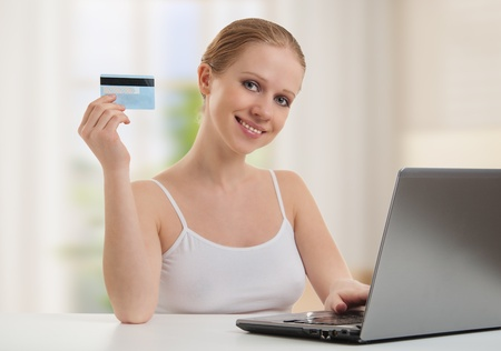 pay bills: girl with a laptop makes a payment online  Stock Photo