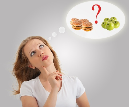 eating questions: woman makes choice  healthy, unhealthy foods, apple and hamburger on a modern conceptual background Stock Photo