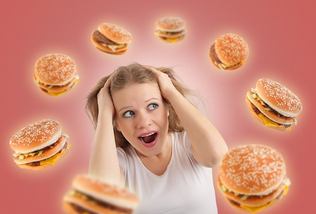 high calorie foods: diet concept. young woman, burgers  Stock Photo