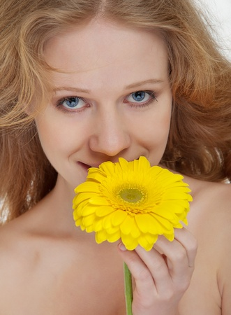 beautiful blonde girl with yellow gerbera flower photo