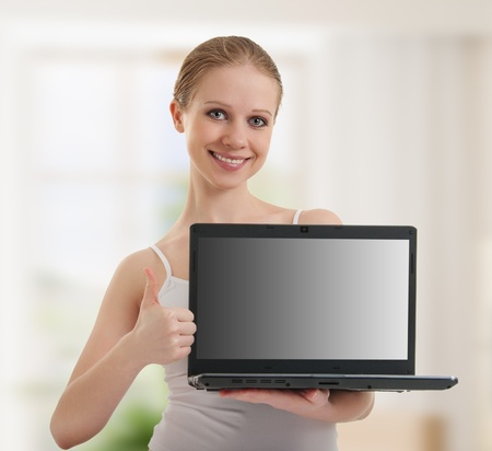 young  woman showing  laptop, empty  screen photo