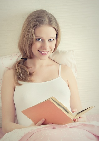 beautiful girl is resting in bed, reading a book  photo