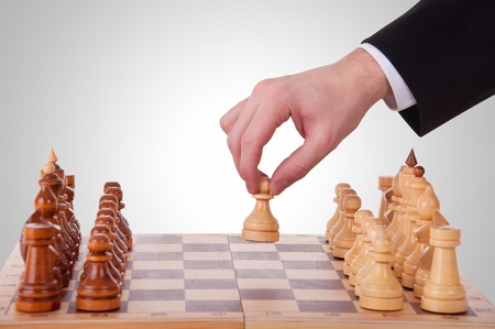 hand move: chess. The first step. hand chess and a chess board Stock Photo