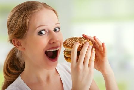 high calorie foods: attractive  woman eats unhealthy food, hamburger Stock Photo