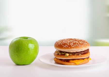 healthy, unhealthy food. Diet concept: apple, burger photo