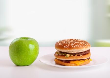 decis�es: saud�vel, alimentos n�o saud�veis. Conceito da dieta: ma��, hamb�rguer