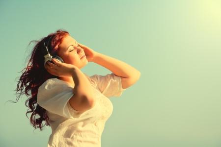 escuchando musica: hermosa chica pelirroja le gusta la música con los auriculares