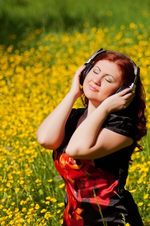 redhead pretty girl with headphones listening to music  photo