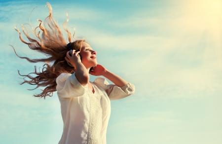listening to music: hermosa chica con volar el pelo rubio, escuchar m�sica
