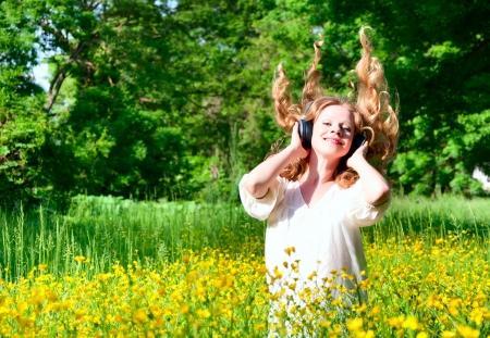 flowing hair: beautiful girl in headphones enjoying the music in nature