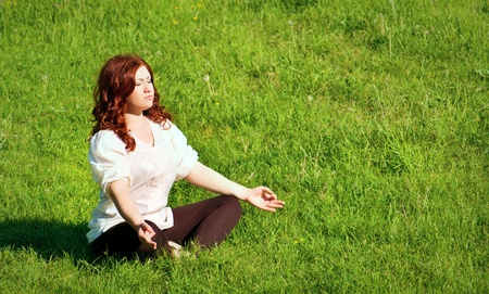 young redhead woman practicing yoga lotus pose outdoors on the grass on the lawn in the park photo