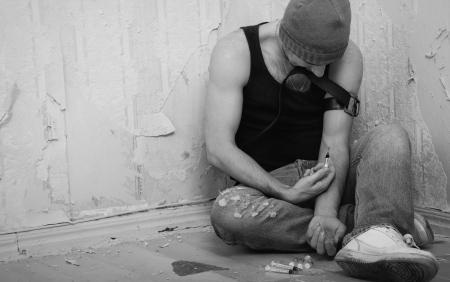 droga: adicto con jeringas y drogas sentados en el suelo