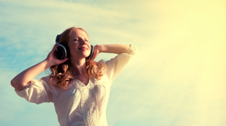 beautiful girl listening to music on headphones in sky photo