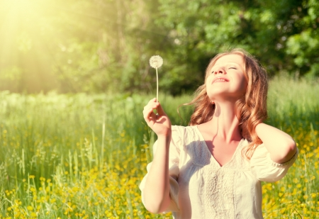 beautiful girl with dandelion enjoying the summer sun  photo