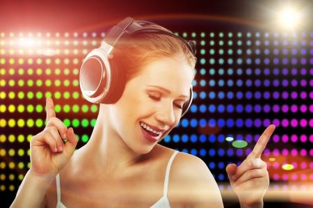 girl with headphones in nightclub dancing photo