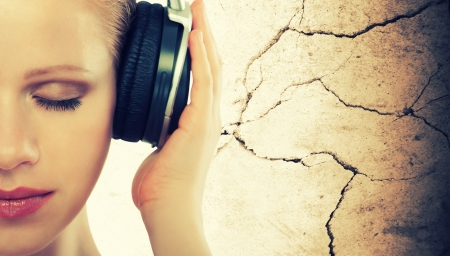 woman listening to music: music concept. half of the face woman with headphones