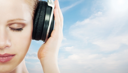 music concept. half of the face woman with headphones on the sky background, clouds Stock Photo - 14721817