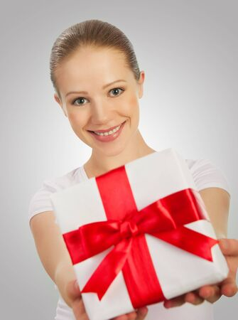 beautiful young woman with a Christmas gift with red ribbon in their hands on a gray background photo