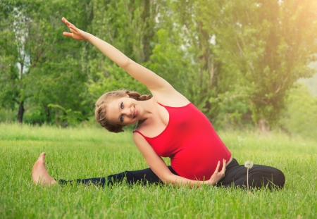 pregnancy yoga: healthy pregnant woman doing yoga in nature outdoors
