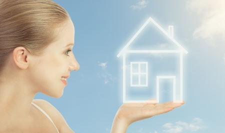 Concept housing, mortgage. woman holding in hand  a house in the sky  photo