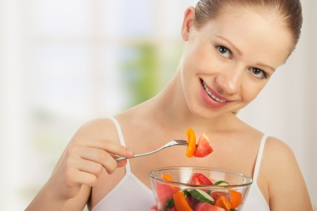 young healthy woman eats vegetable vegetarian salad photo