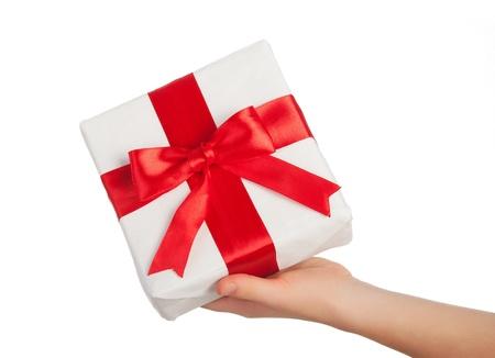 dar un regalo: mano con un regalo con una cinta roja sobre fondo blanco Foto de archivo
