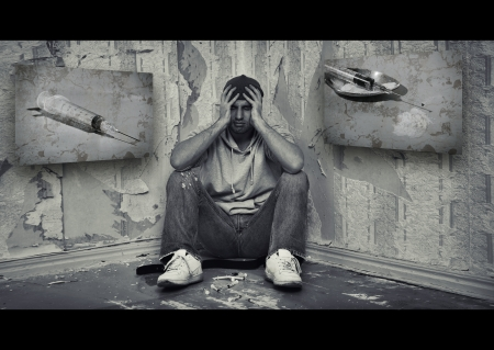concept of the dangers of drugs. drug addict man sitting on the floor with drugs photo