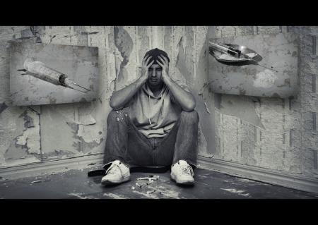 concept van de gevaren van drugs. drugsverslaafde man zittend op de vloer met drugs Stockfoto