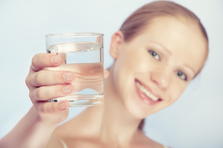 girl drinking water: face of a young healthy woman and a glass of clean water