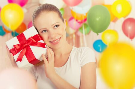 young woman with a gift on a holiday with colorful balloons photo