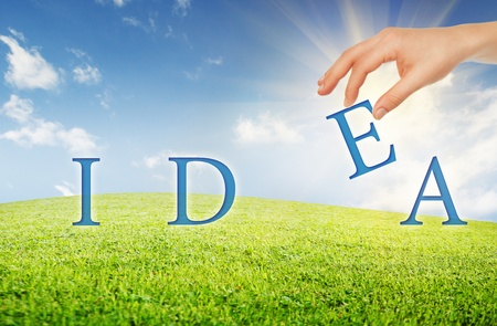 concept, an idea. human hand makes the idea of the letters of the word on the background of sky and grass photo