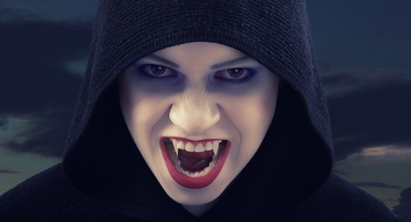 angry woman vampire against the dark sky photo