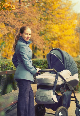 young mother with a pram on a walk in the park in autumn photo