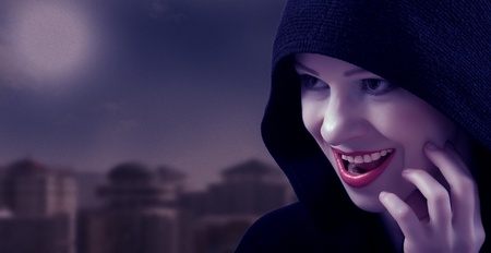 beautiful witch in a black hood on the day of Halloween photo