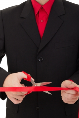grand opening ceremony. man cutting the red ribbon with scissors photo