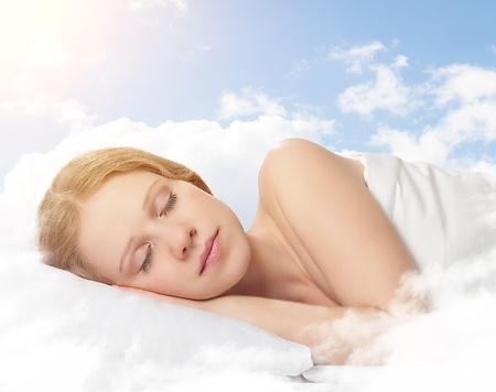durmiendo: retrato de una bella mujer joven que duerme en una nube en el cielo